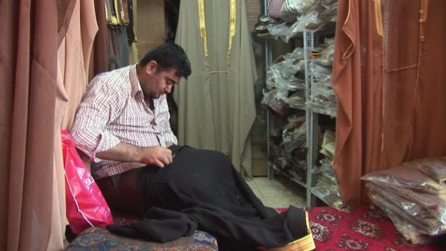 vídeos de stock e filmes b-roll de 20th jul 2009 ws tailor sewing in workshop / baghdad iraq - só um homem de idade mediana