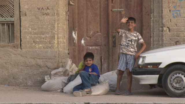 20th jul 2009 three boys on sidewalk in shanasheel district / basra, iraq - basra stock-videos und b-roll-filmmaterial