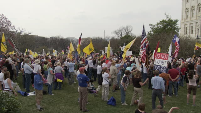 mar-2010 crowd with flags and signs protesting health care bill next to us capitol building. washington monument can be seen in the background /... - 2010 stock videos & royalty-free footage