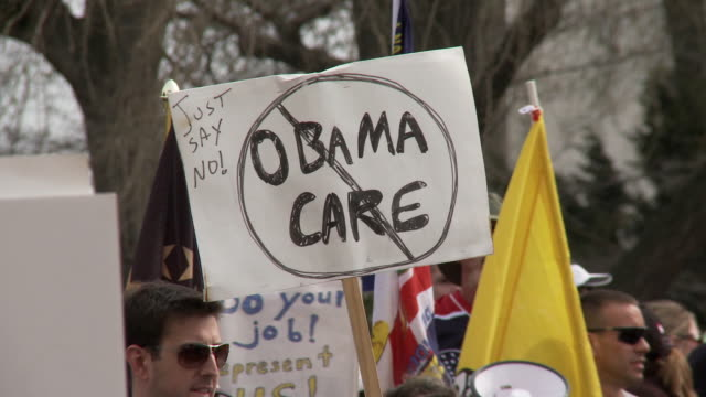 mar-2010 protestors holding sign reading obama care with circle and slash / washington dc, usa / audio - 2010 個影片檔及 b 捲影像