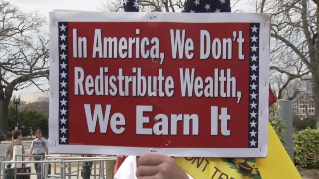 stockvideo's en b-roll-footage met mar-2010 protestors holding sign saying in america, we don't redistribute wealth, we earn it / washington dc, usa / audio - 2010
