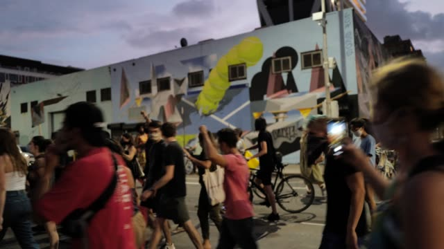 24th 2020: protestors march past a live band playing on a street corner. the 55th night of the george floyd vigil at mccarren park included live... - rebellion stock videos & royalty-free footage