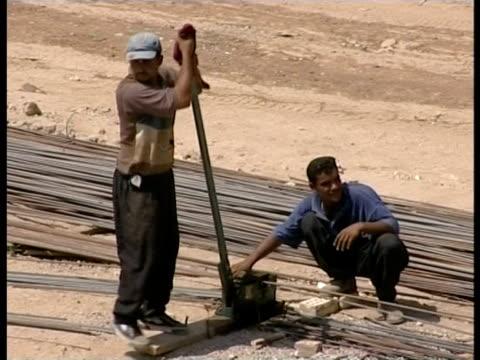 vídeos de stock e filmes b-roll de 24th feb 2009 montage men working on construction site / baghdad iraq - só um homem de idade mediana