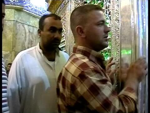 24th feb 2009 montage shia pilgrims kissing wall of mosque / baghdad, iraq - 信者点の映像素材/bロール