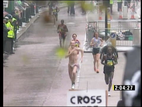 London EXT Start of London Marathon TGV Mass of runners CBV Woman applauding runners Man in silly costume running towards interview SOT Applauding...