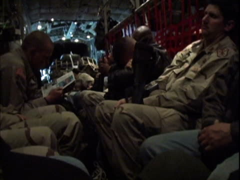 25th dec 2003 ms pan contractors and us soldiers flying to iraq on c130 hercules / iraq / audio - 2003 bildbanksvideor och videomaterial från bakom kulisserna