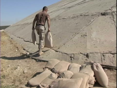 stockvideo's en b-roll-footage met 25th dec 2003 montage soldiers carrying sandbags up side of hangar to make gun placement / lsa anaconda, iraq / audio - 2003