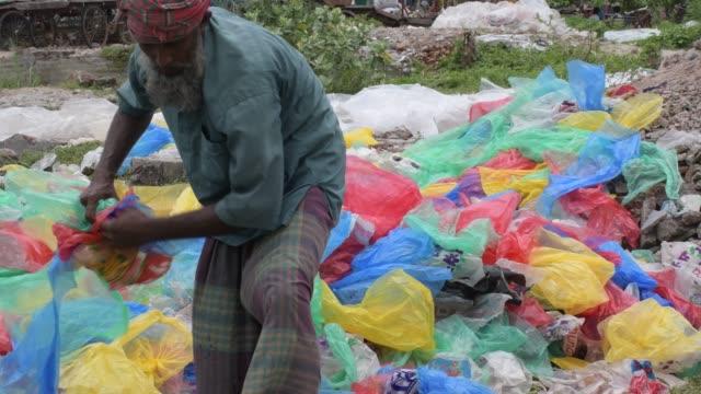 vídeos de stock e filmes b-roll de 26th june 2020: bangladeshi worker prepares plastic bags to dry near the buriganga river in dhaka - saco de plástico