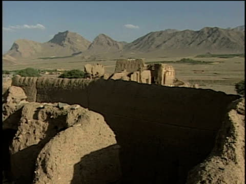 27th april 2000 ws pan remains of ancient city and caravanserai in desert area / mashad ardehal, kashan, iran - inn stock videos & royalty-free footage