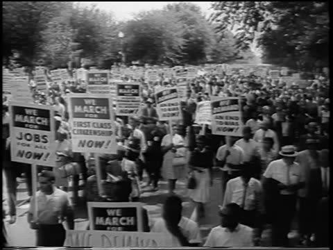 28th august 1963, high angle large crowd marching with signs on wide street / march on washington / newsreel - ワシントン大行進点の映像素材/bロール