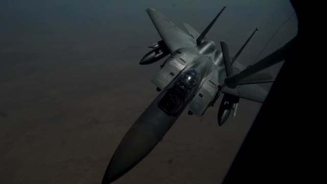A 28th Expeditionary Air Refueling Squadron KC135 Stratotanker provides aerial refueling over Qatar to F15 Eagle in support of Operation Inherent...