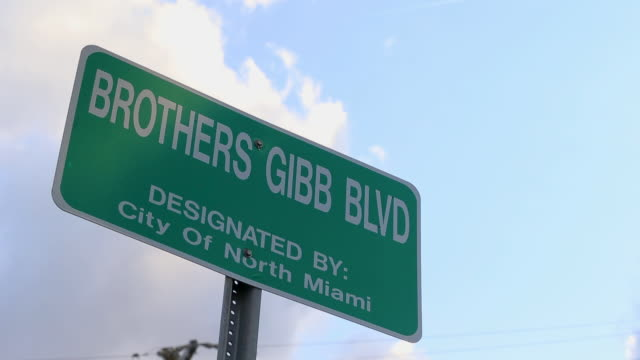 vídeos y material grabado en eventos de stock de 2nd 2018: low angle timelapse shot of a road sign depicting the brothers gibb blvd in honor of the bee gees - condado de miami dade