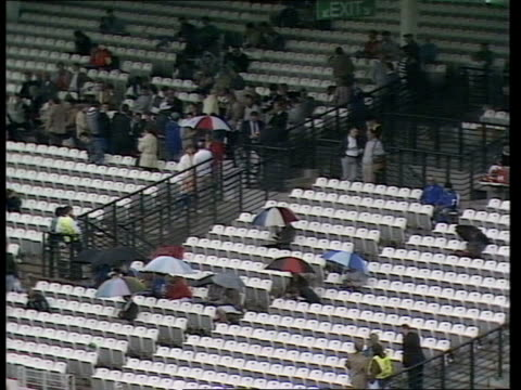 rain prevents play england london lord's cricket ground nw8 tcms wicket under covers tms few people in stands with umbrellas up ms two men under 1... - lords cricket ground stock videos and b-roll footage