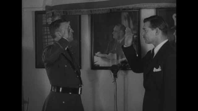 2shot Colonel Malcolm P Andruss gives oath Clark Gable right hand raised listens intently replies 'I do' / CU Gable listening to oath replies 'I do'...
