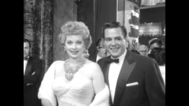 2shot comedienne lucille ball and bandleader desi arnaz pose as they arrive for movie premiere of a star is born in hollywood / spectators in... - film premiere stock videos & royalty-free footage