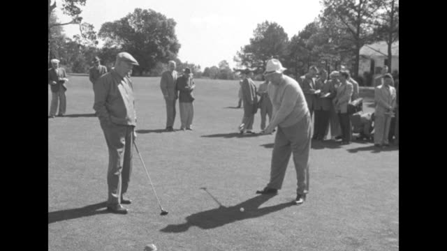 2shot Dwight Eisenhower and Robert Taft stand on fairway at Augusta National Golf Club Taft wears floppy hat Eisenhower wears newsboy cap / Taft tees...