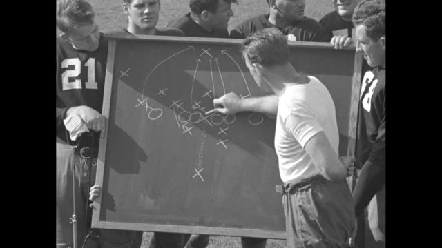 2shot Notre Dame Fighting Irish football coach Frank Leahy stands with team captain Paul Lillis on football field / montage team watches as Leahy...