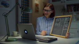 30s female teacher in glasses writing simple mathematical equations on chalk board with white chalk looking at laptop at home. Online education process. Side view of teacher talking.