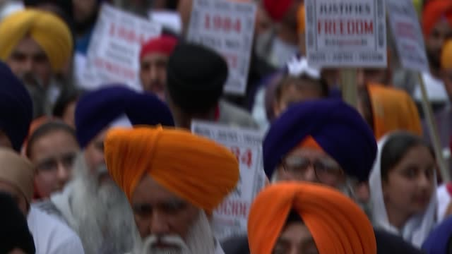 Sikhs march through London ENGLAND London Hyde Park EXT Various of Sikhs marching with placards remembering massacre of 1984
