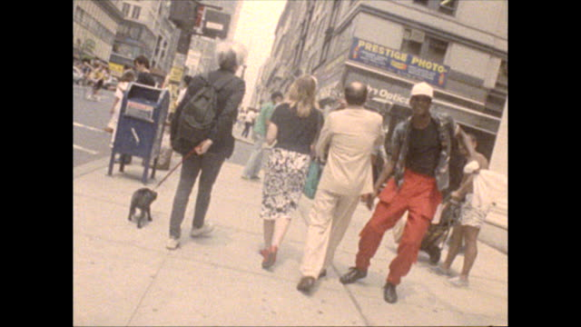 35th street and 5th Avenue Warhol accompanied by director Russ Karel and a young woman walks his dog on a leash passes by man who starts dancing and...