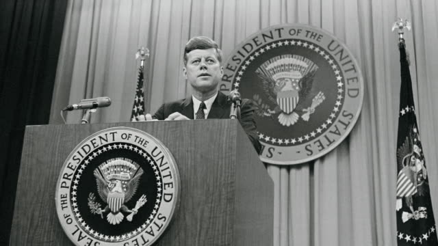 35th u.s. president john f. kennedy stands at a rostrum as he conducts a press conference. - john f. kennedy politik stock-videos und b-roll-filmmaterial