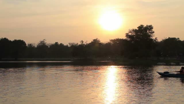 ฺboys canoeing on the lake at sunset. - rowing stock videos & royalty-free footage