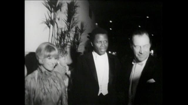 stockvideo's en b-roll-footage met 37th annual academy awards outside cars leaving santa monica civic auditorium exterior oscar party judy garland exits the auditorium ginger rogers... - beverly hilton hotel