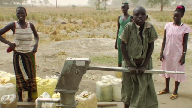 3rd march 2009 slo mo ms teenage girl pumping water from well / duk payuel jonglei sudan - スーダン点の映像素材/bロール