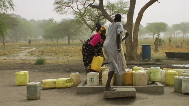 3rd March 2009 WS ZI MS PAN Woman pumping water and another woman carrying jug on head / Duk Payuel Jonglei Sudan