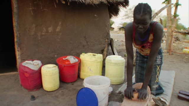 3rd march 2009 young woman grinding sorghum into flour / duk payuel, jonglei, sudan - sorghum stock videos & royalty-free footage
