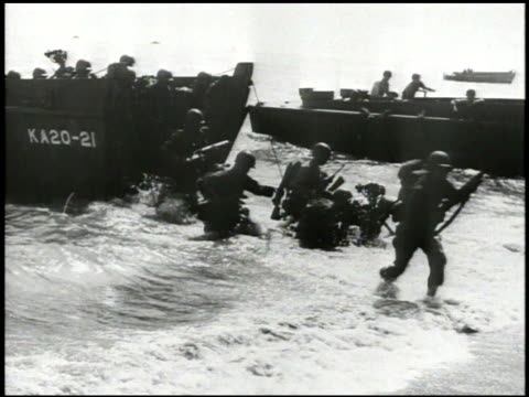 S 3rd Marines Division infantry soldiers landing on Empress Augusta Bay beach out of landing crafts charging forward truck driving on shore WWII...