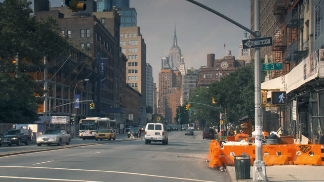 WS 3rd St and Bowery on light traffic day, Empire State Building in background / New York City, USA