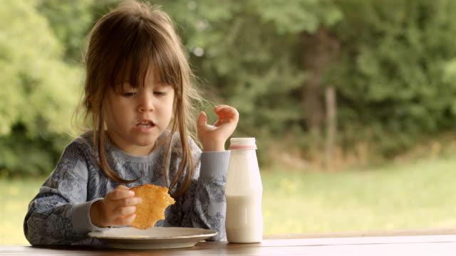 3 anni figlio godendo latte e pane tostato francesi su un bellissimo estate mattina presso La Veranda