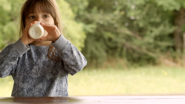 3-Year Old Child Enjoying Milk on a Beautiful Summer Morning at The Porch