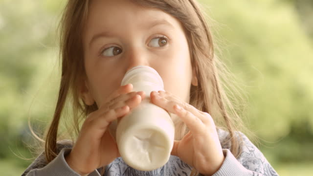 3-year old child enjoying milk on a beautiful summer morning at the porch - yoghurt stock videos and b-roll footage