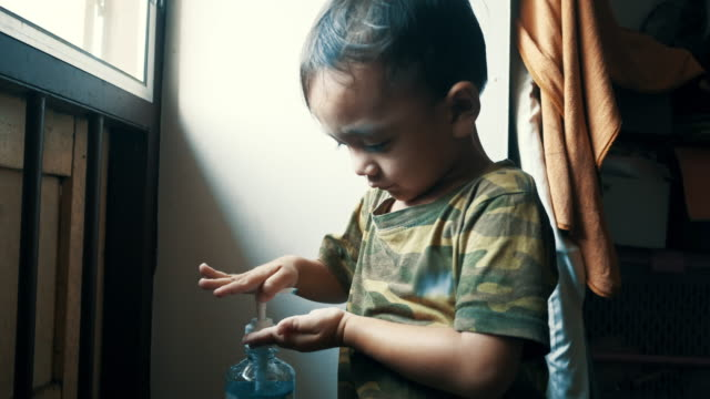 vídeos de stock e filmes b-roll de 3-year-old boy washing his hands with alcohol gel - borrifo