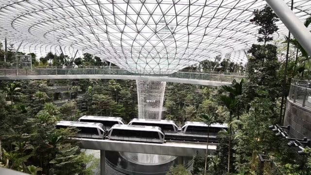 a 40metre indoor waterfall cascading through a steel and glass dome is unveiled at the heart of a vast complex in singapore's main airport - waterfall stock videos & royalty-free footage
