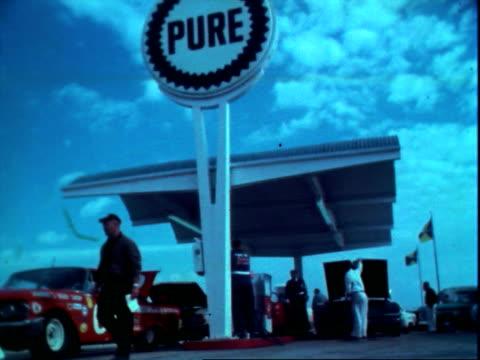 410hp 1963 ford stock car pulling from pure gas station near racetrack at daytona international speedway in daytona / 1963 chevrolet pulling away... - circuito di daytona video stock e b–roll