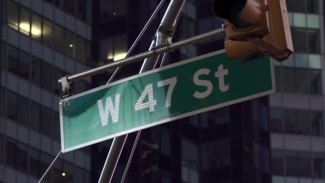 47th street in new york street sign with lights flashing reflecting in the gloss of the sign. - western script stock videos & royalty-free footage