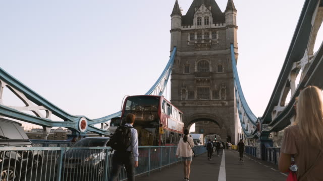 4k 10bit commuters leaving work and heading home over tower bridge and thames river at sunset, london - tower stock videos & royalty-free footage