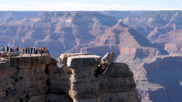 stockvideo's en b-roll-footage met 4k 10bit groups of tourists visiting the grand canyon national park to take photos and selfies of the giant crater and cliffs. - southwest usa