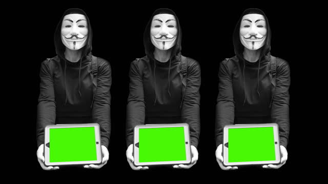 vídeos de stock e filmes b-roll de 4k 10bit scene of male hacker wearing guy fawkes anonymous mask while using laptop tablet with green screen billboard advertising space - crime informático