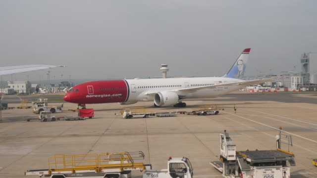 4k 10bit scene of norwegian air shuttle airplane taxiing at london gatwick airport in crawley, u.k - commercial airplane stock videos & royalty-free footage