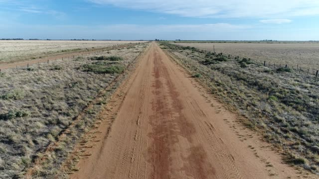 4k aerial pov along dirt road in the outback - long点の映像素材/bロール