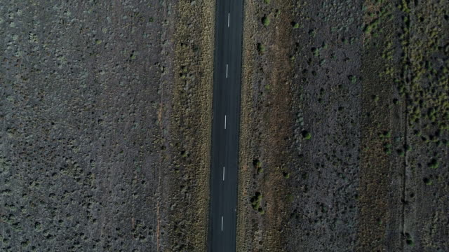 4k aerial car driving along black road - drought stock videos & royalty-free footage