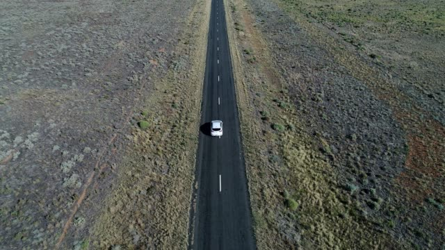 4k aerial car driving on black road in desert - activity stock videos & royalty-free footage