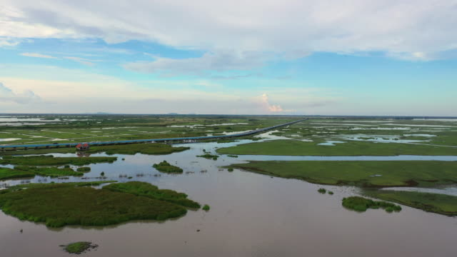 4k luft-drohnen-film fliegen über autobahnbrücke über natursee in pattalung, thailand - hd format stock-videos und b-roll-filmmaterial