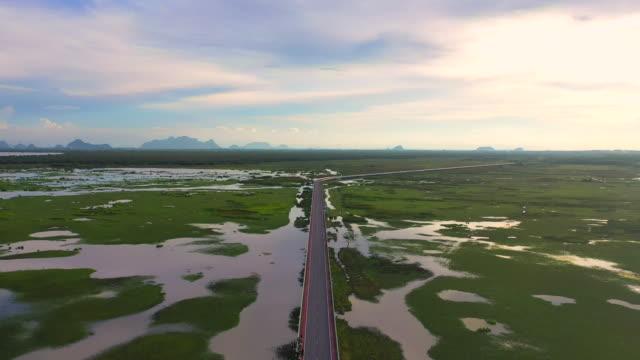 stockvideo's en b-roll-footage met 4k luchtfoto drone film vliegen over de snelwegbrug over het natuur meer in pattalung, thailand - kust karakteristiek