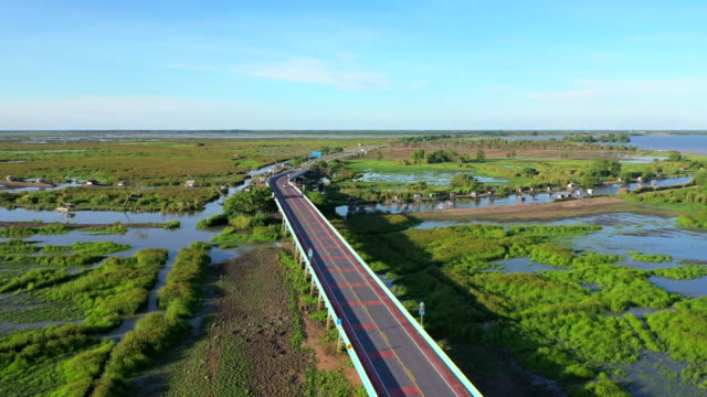 4k aerial drone movie fly over highway bridge across nature lake in pattalung, thailand - coastal feature stock videos & royalty-free footage
