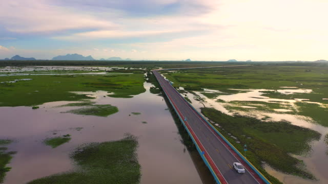 4k aerial drone movie fly over highway bridge across nature lake in pattalung, thailand - ship's bridge stock videos & royalty-free footage